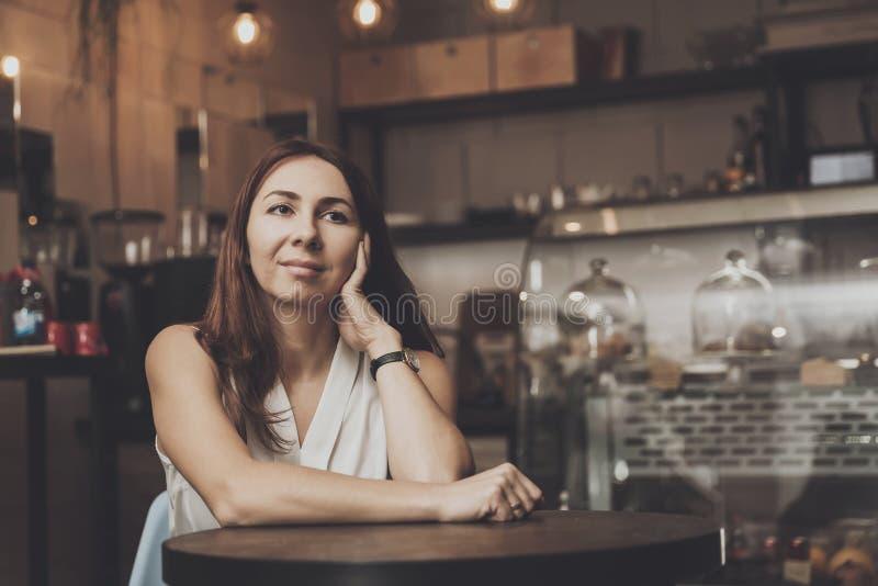 Chica joven que se sienta en un café que aguarda a un hombre joven imagenes de archivo