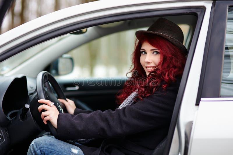 Chica joven que se sienta en un coche imagenes de archivo