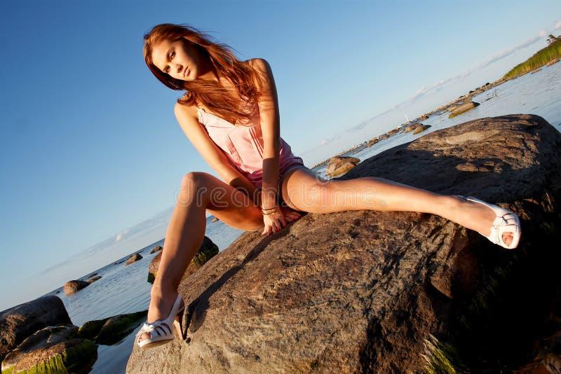 Chica joven que se sienta en una piedra imagen de archivo libre de regalías