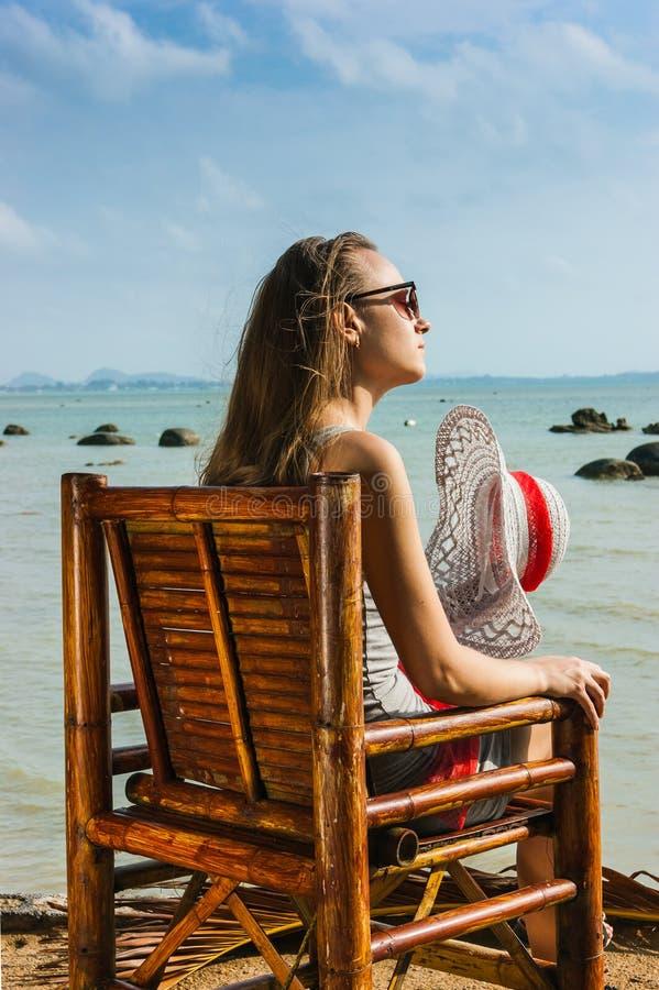 Chica joven que se sienta en una silla cerca del mar foto de archivo