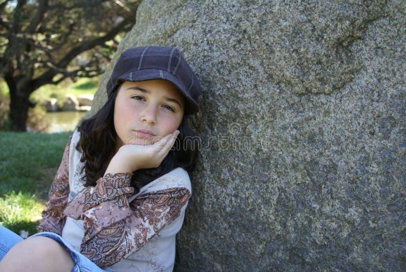 Chica joven que se sienta por la roca en parque foto de archivo libre de regalías
