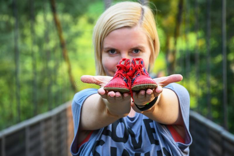 Chica joven que se sostiene en ambos pequeños zapatos de bebé rojos de los brazos extendidos fotos de archivo