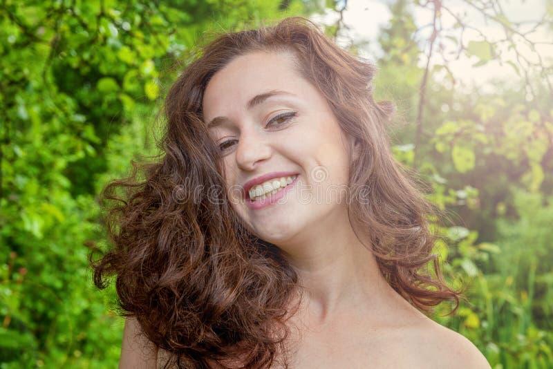 Chica joven que sonríe en parque imagenes de archivo