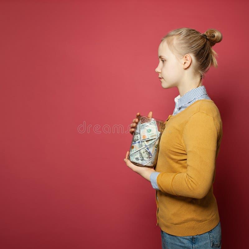 Chica joven que sostiene el dinero Sueldo del trabajo a tiempo parcial, tarifas de la universidad, responsabilidad y concepto de  fotografía de archivo libre de regalías