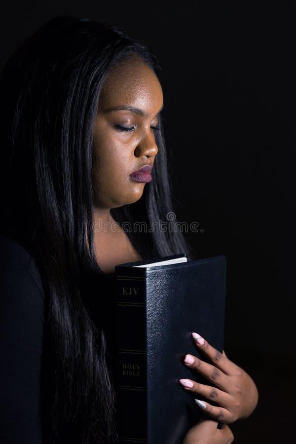 Chica joven que sostiene la biblia cerca de su corazón imagen de archivo libre de regalías