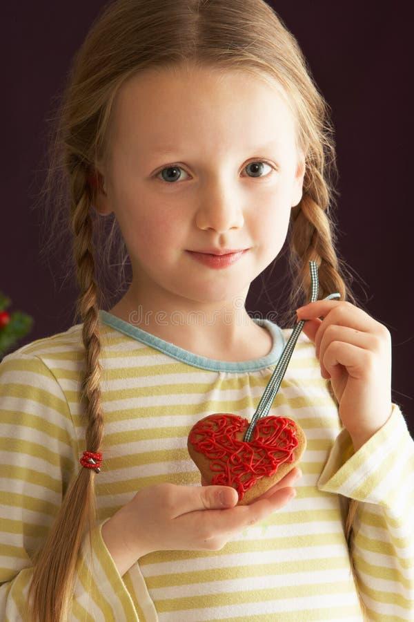 Chica joven que sostiene la galleta en forma de corazón en estudio foto de archivo libre de regalías