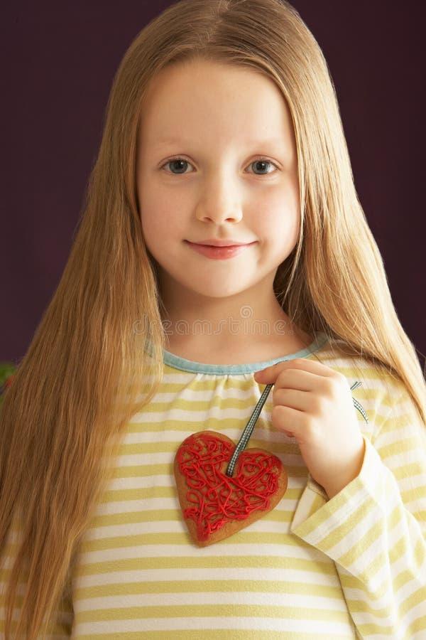 Chica joven que sostiene la galleta en forma de corazón en estudio imagenes de archivo