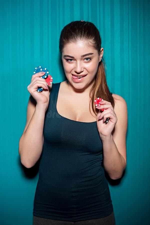 Chica joven que sostiene las fichas de póker en fondo azul imagen de archivo libre de regalías