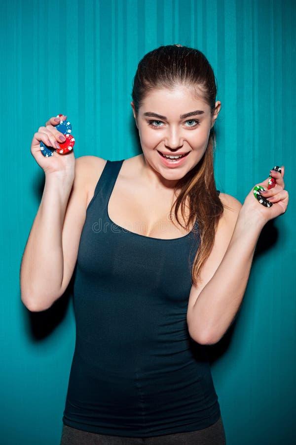 Chica joven que sostiene las fichas de póker en fondo azul imagenes de archivo
