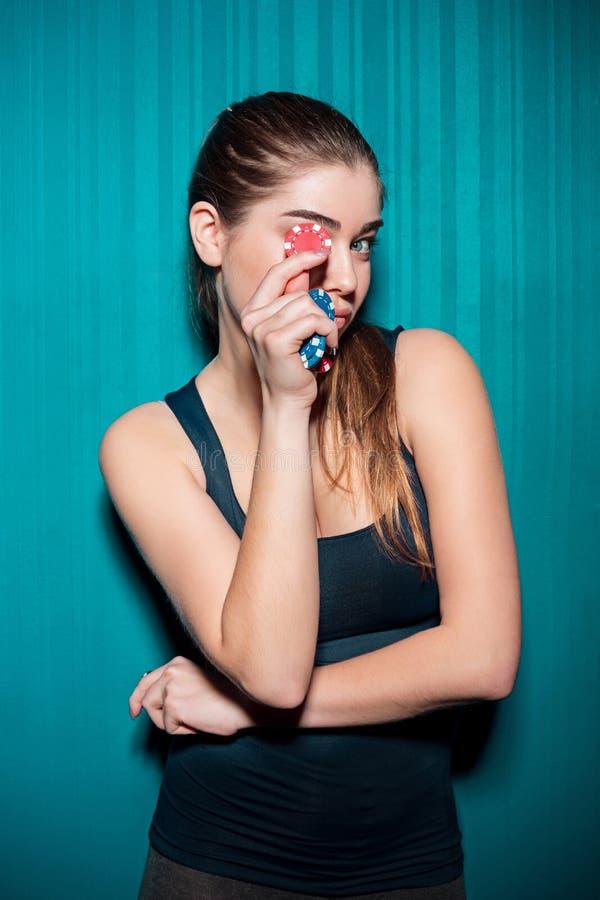 Chica joven que sostiene las fichas de póker en fondo azul fotos de archivo libres de regalías