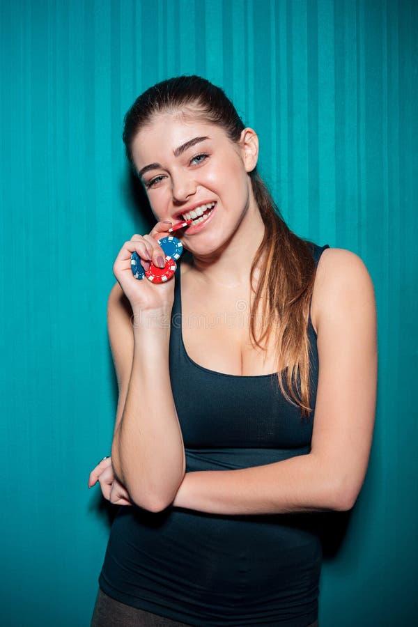 Chica joven que sostiene las fichas de póker en fondo azul foto de archivo libre de regalías