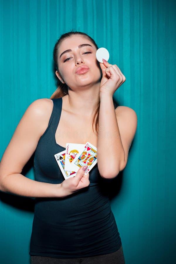 Chica joven que sostiene las fichas de póker en fondo azul imágenes de archivo libres de regalías