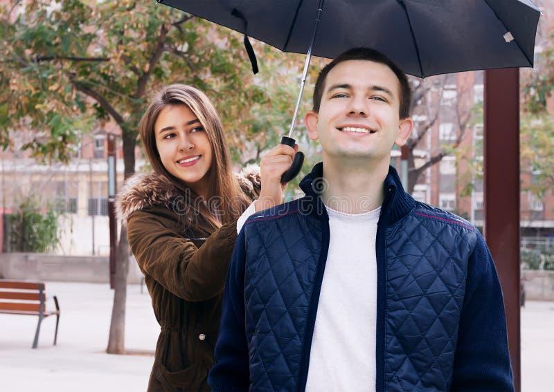 Chica joven que sostiene un paraguas sobre el hombre hermoso fotografía de archivo libre de regalías