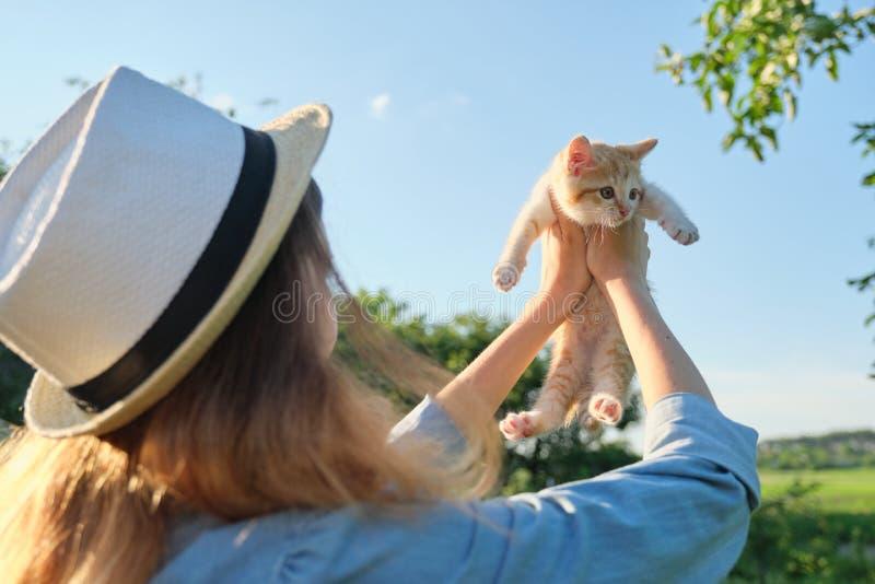 Chica joven que sostiene un pequeño gatito rojo en el jardín imagen de archivo libre de regalías