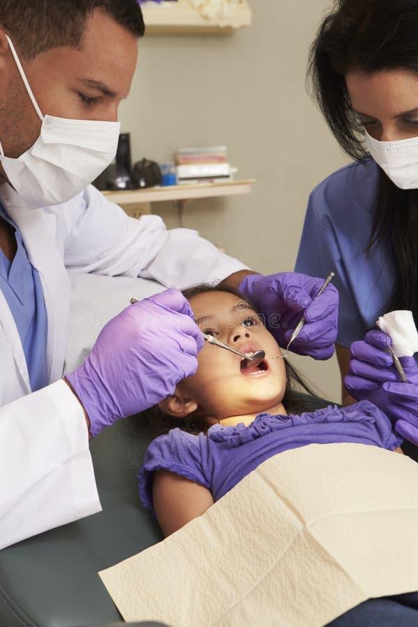 Chica joven que tiene control para arriba en la cirugía de los dentistas imagenes de archivo