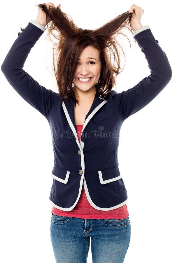 Chica joven que tira de su pelo en el entusiasmo fotografía de archivo libre de regalías
