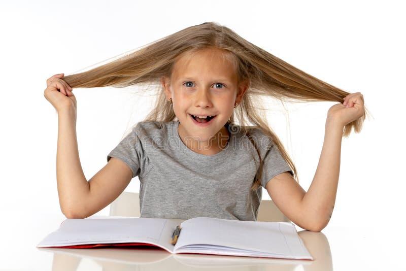 Chica joven que tira de su pelo en la tensión y sobre concepto trabajado de la educación imagen de archivo