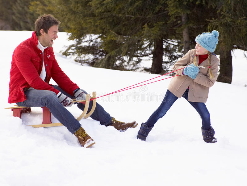 Chica joven que tira del padre a través de nieve en el trineo fotografía de archivo