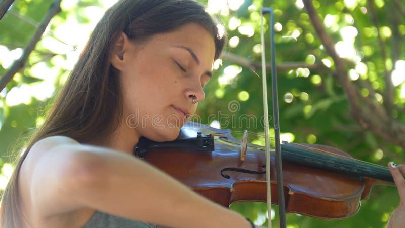 Chica joven que toca el violín del vintage en la naturaleza fotos de archivo libres de regalías