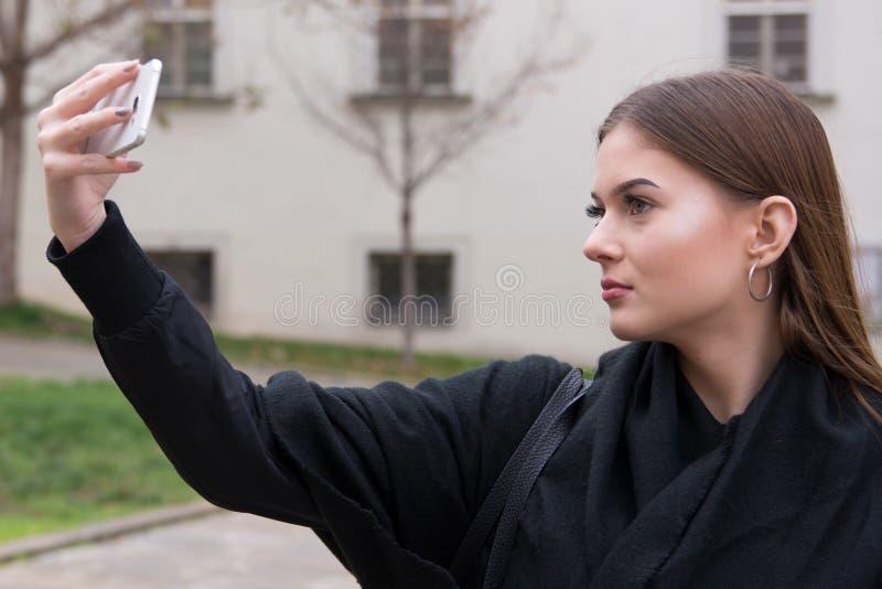 Chica joven que toma el selfie por smartphone en la calle foto de archivo