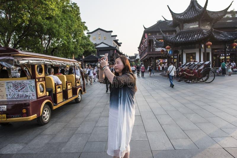 Chica joven que toma una imagen con el teléfono móvil en la plaza del templo de Confucio fotos de archivo