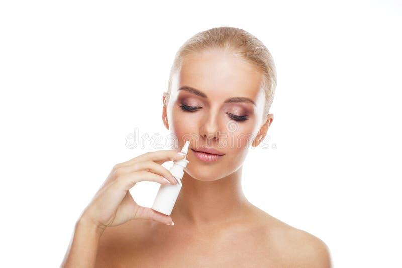 Chica joven que usa el aerosol nosal del espray y descensos aislados en blanco Enfermedad de los mocos, de la alergia, del frío y foto de archivo