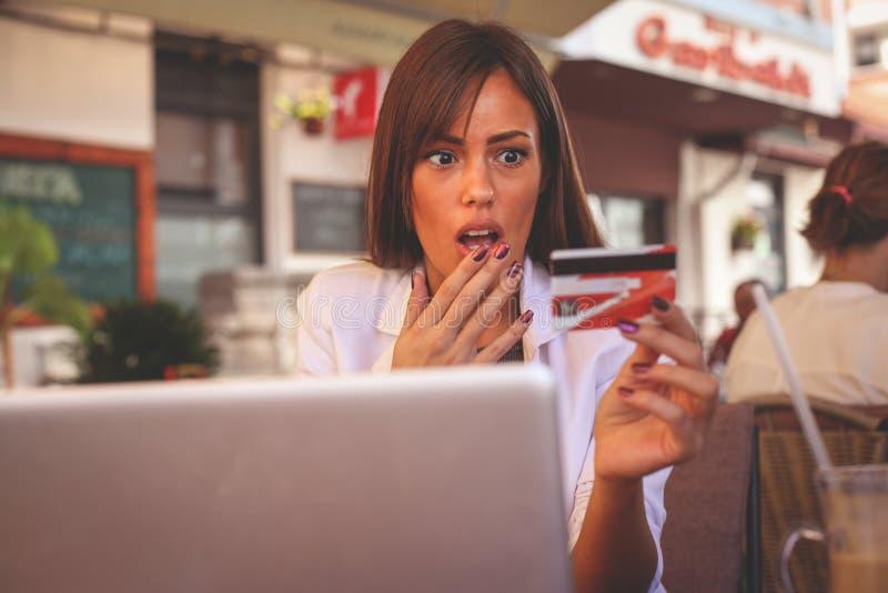 Chica joven que usa la tarjeta de crédito La muchacha era arruinada foto de archivo