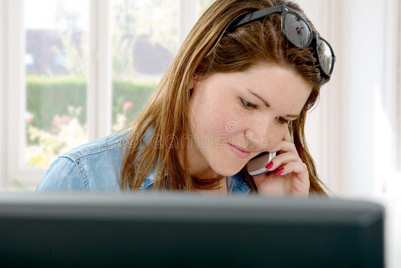 Chica joven que usa su teléfono móvil en la oficina imágenes de archivo libres de regalías