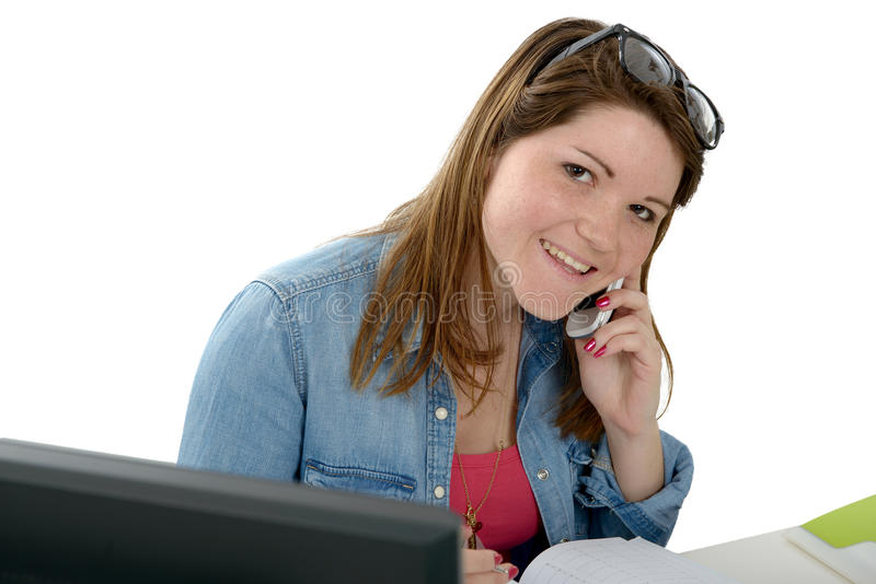 Chica joven que usa su teléfono móvil en la oficina foto de archivo