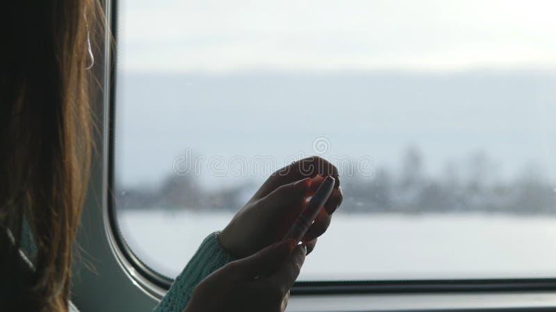 Chica joven que viaja en un tren y que usa el teléfono móvil La mujer hermosa envía un mensaje del smartphone atractivo imagen de archivo libre de regalías