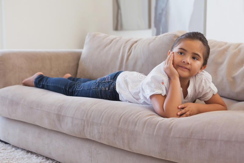 Chica joven relajada que miente en el sofá foto de archivo