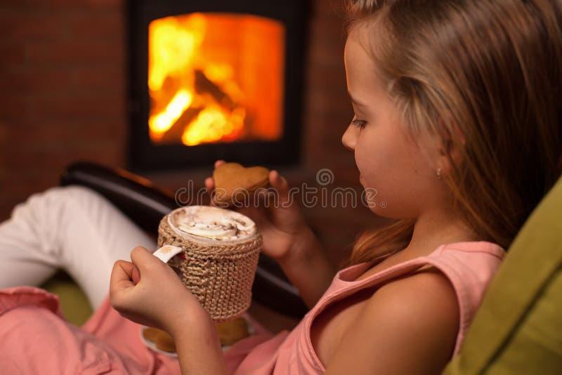 Chica joven sentándose delante de la chimenea con un chocolate caliente imágenes de archivo libres de regalías
