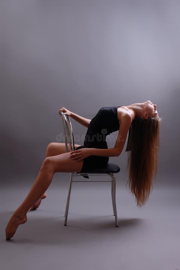 Chica joven sexual en una silla fotografía de archivo libre de regalías
