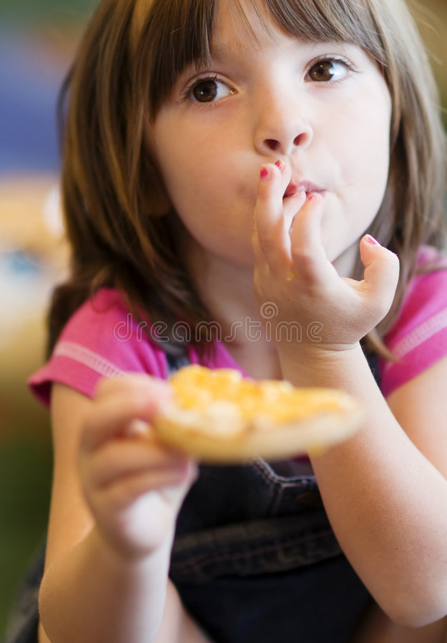 Chica joven sonriente bonita que come un mollete foto de archivo libre de regalías