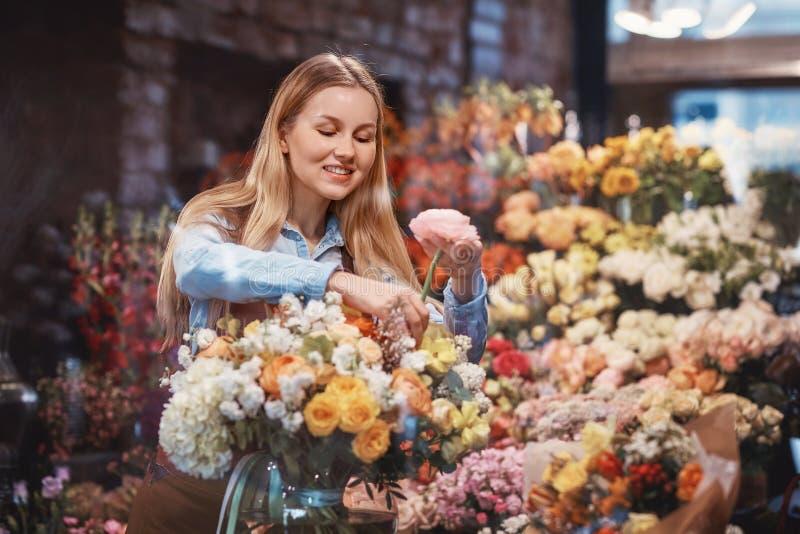 Chica joven sonriente con las flores foto de archivo