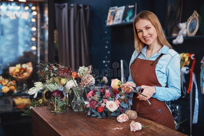 Chica joven sonriente con las flores imagen de archivo