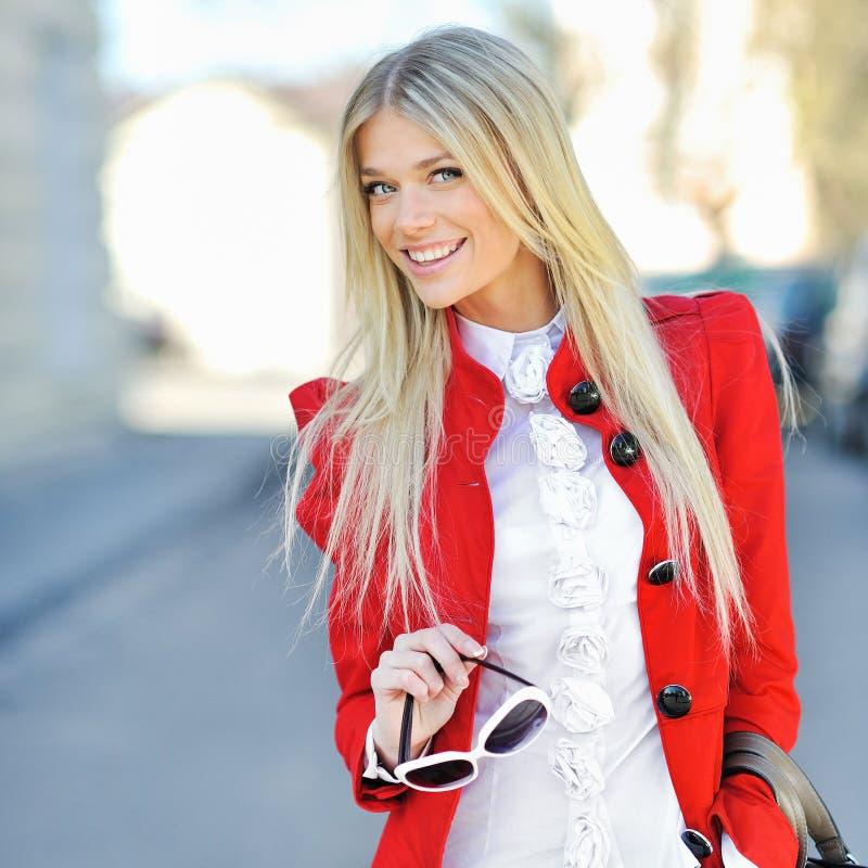 Chica joven sonriente de moda en vestido rojo con el bolso al aire libre imagenes de archivo
