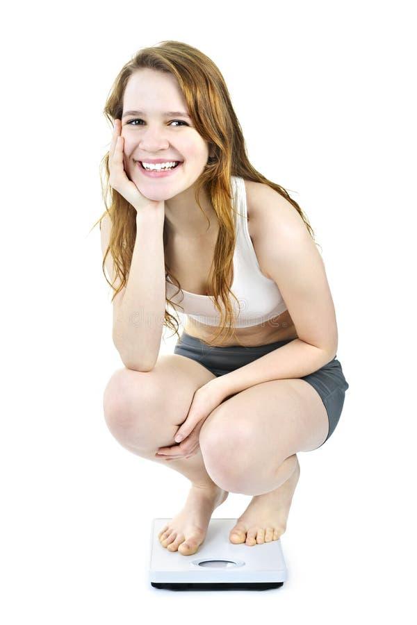 Chica joven sonriente en báscula de baño imagen de archivo
