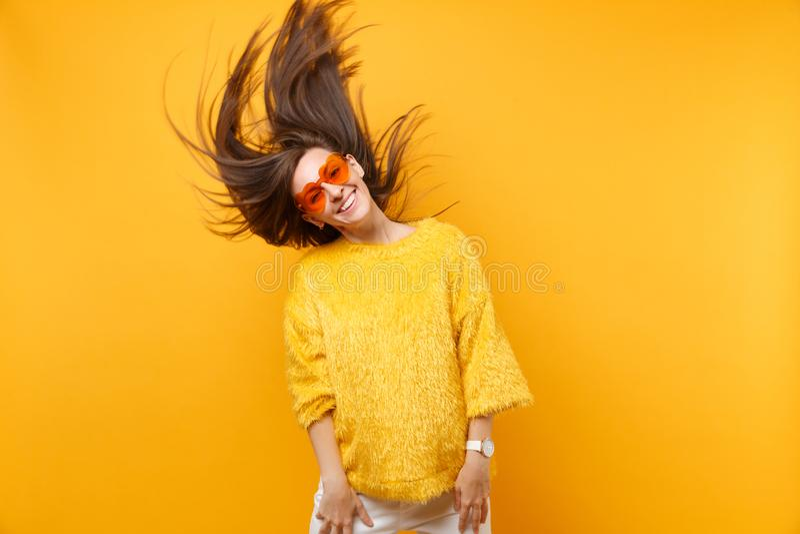Chica joven sonriente en el suéter de la piel, vidrios anaranjados del corazón gritando engañar alrededor en el estudio que salta fotografía de archivo