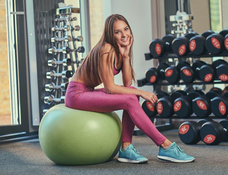 Chica joven sonriente en la ropa de deportes rosada que se sienta en una bola de la aptitud en el gimnasio fotografía de archivo libre de regalías