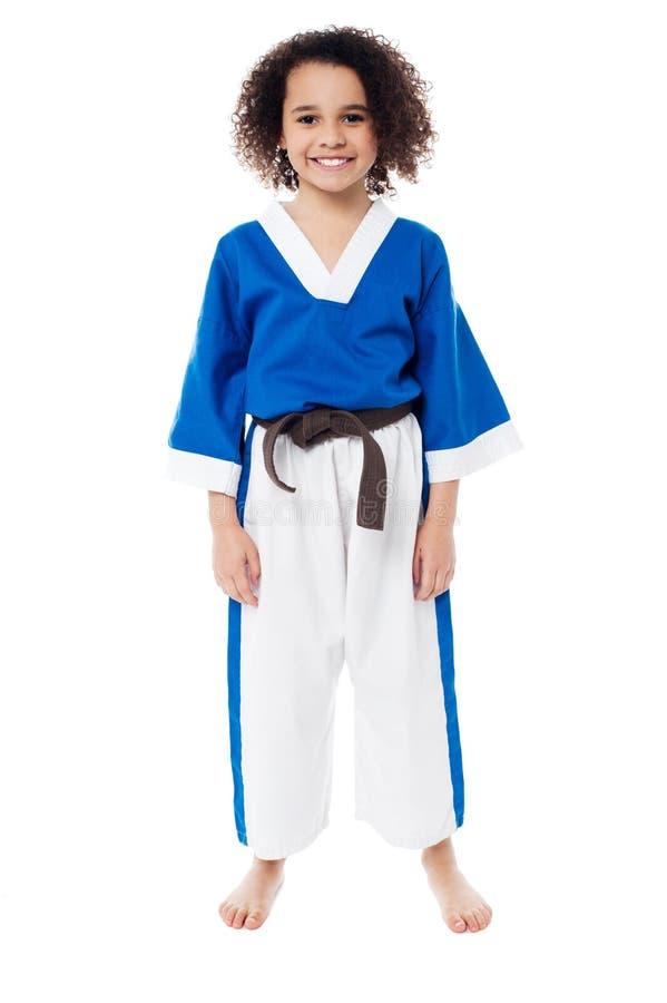 Chica joven sonriente en uniforme del karate imagenes de archivo
