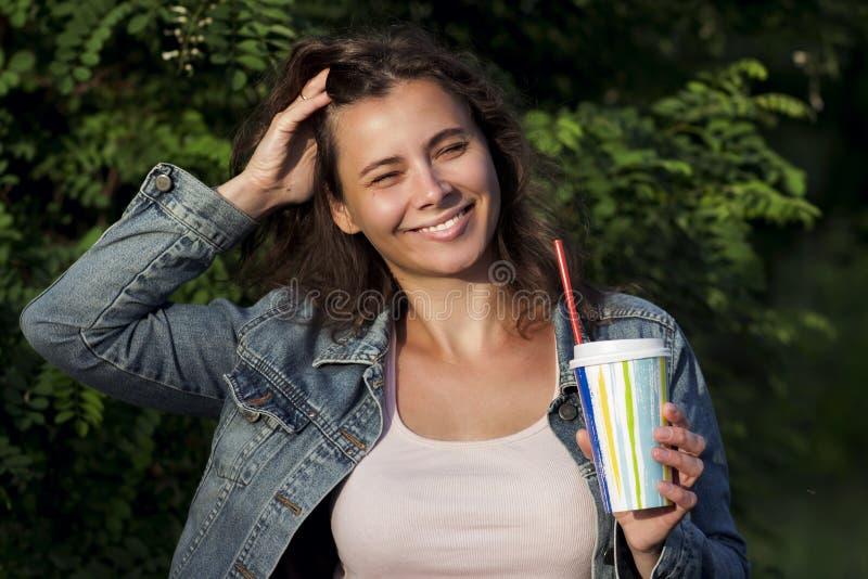 Chica joven sonriente feliz con la bebida en vidrio con la paja en parque del verano imagen de archivo