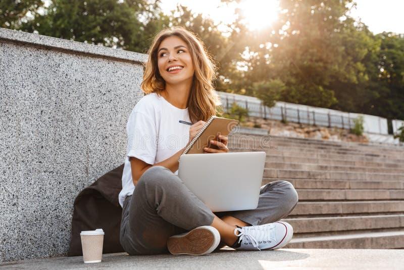 Chica joven sonriente que hace notas en libreta imagenes de archivo