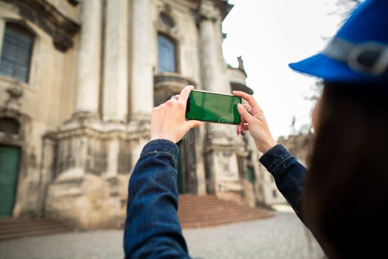Chica joven sonriente que toma las imágenes de los monumentos arquitectónicos de la ciudad vieja Lviv ucrania foto de archivo