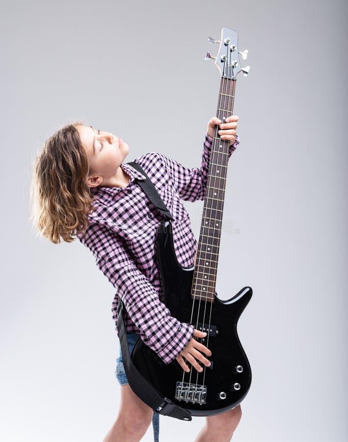 Chica joven talentosa con un regalo para la música de la guitarra foto de archivo