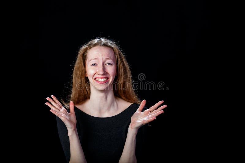 Chica joven triste con el pelo rubio que llora y separada sus manos en los lados foto de archivo