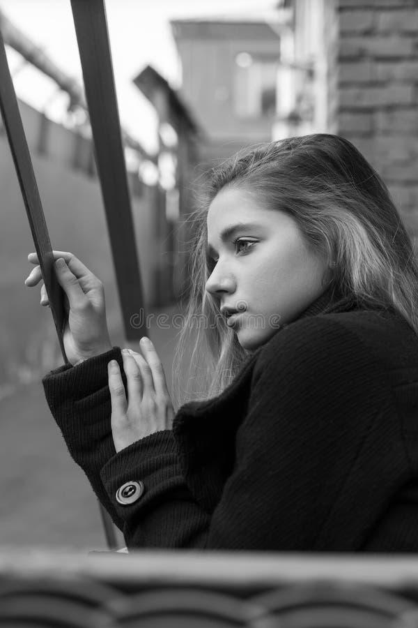 Chica joven triste en la capa negra que se sienta en las escaleras con el fondo urbano del vintage Concepto de soledad foto de archivo libre de regalías