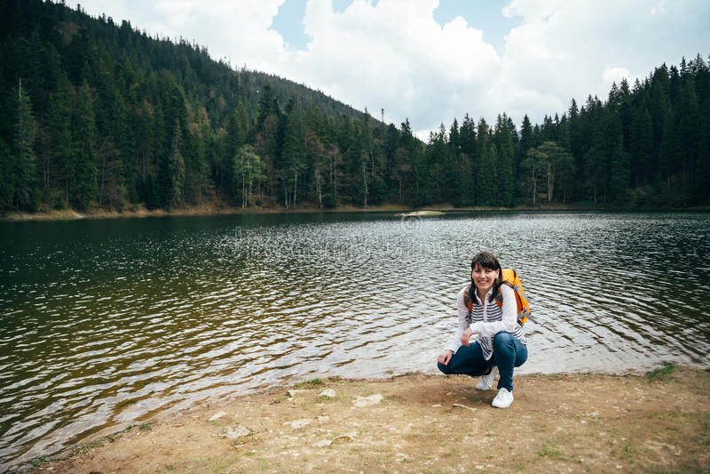 Chica joven, turista con la mochila anaranjada que se sienta en el banco del lago grande de la montaña rodeado por estafa del des fotografía de archivo libre de regalías