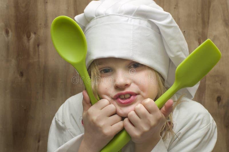 Chica joven vestida como cocinero con las cucharas verdes del silicón en de madera foto de archivo
