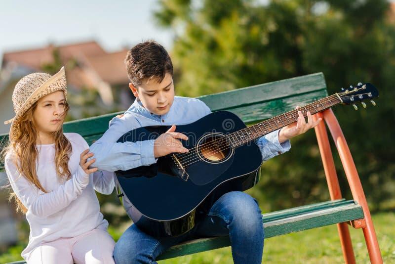 Chica joven y muchacho con la guitarra que se sienta en el banco en parque Amor de los ni?os imagen de archivo libre de regalías